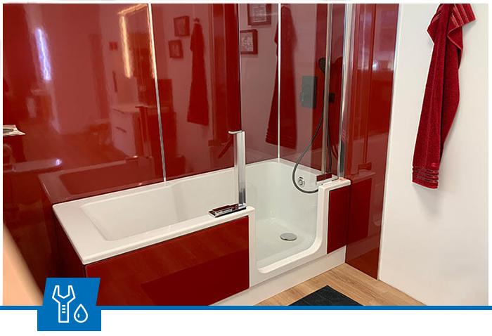 Rotes Badezimmer mit einer Badewanne mit Duschfunktion von Sanitär Fritz